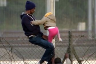 A-migrant-straddling-a-fence-with-a-young-child-at-Calais
